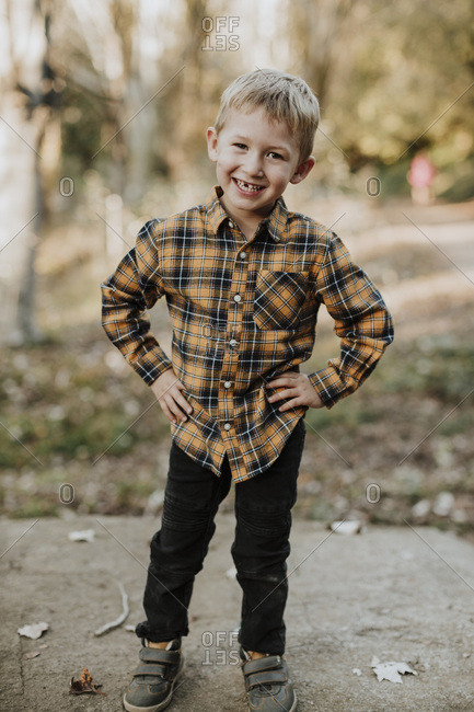 Smiling boy with hand on hip standing in forest