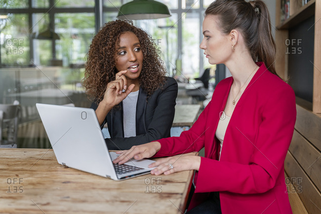 Young businesswoman explaining business strategy to colleague in office cafeteria