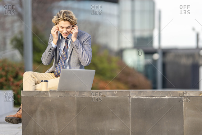 Businessman adjusting in-ear headphones while working on laptop sitting outdoors