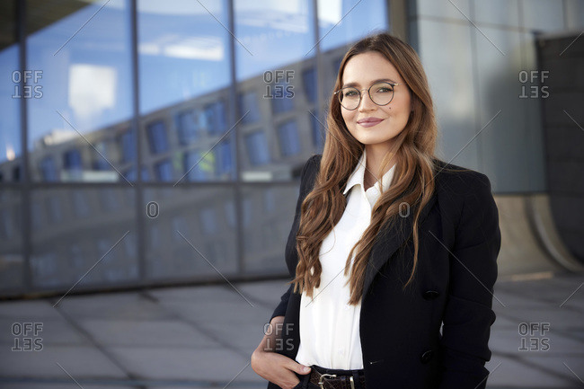Confident businesswoman wearing eyeglasses with hand in pocket standing outdoors