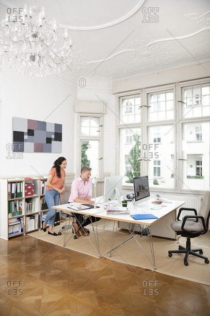 Businessman and female colleague discussing over computer during office meeting