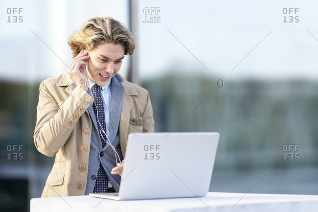 Businessman wearing in-ear headphones while working on laptop standing outdoors