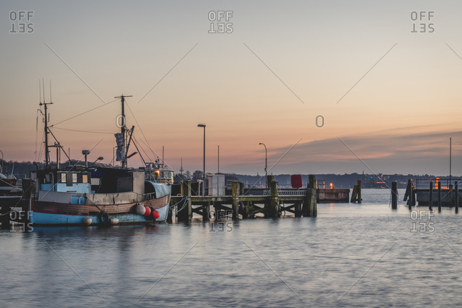 Germany- Schleswig-Holstein- Heikendorf- Fishing boats moored in harbor at dusk