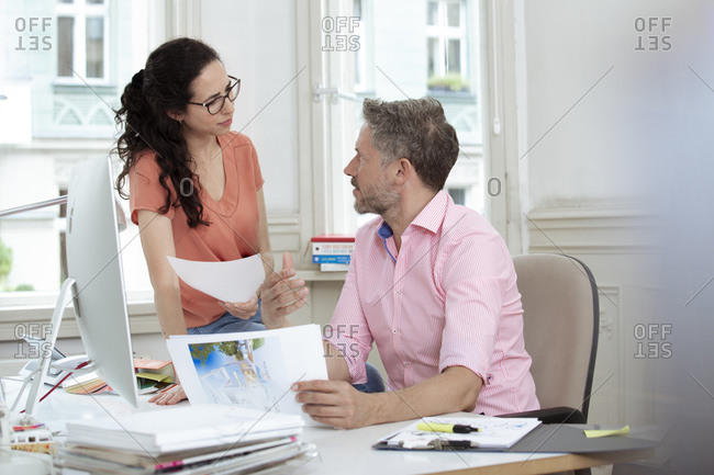 Businessman talking with female colleague during discussion in office meeting