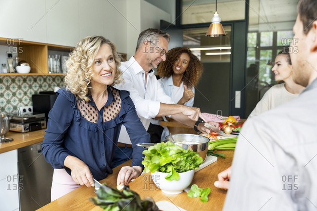 Businesswoman cutting vegetable while talking to colleagues in office kitchen