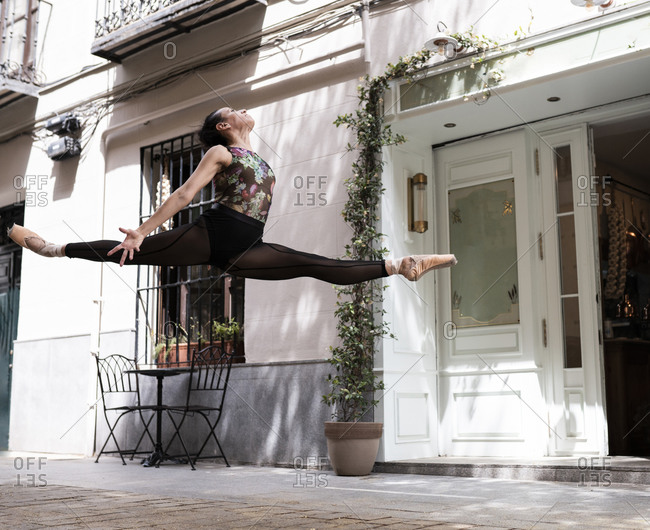 Female dancer with legs outstretched jumping while dancing against building