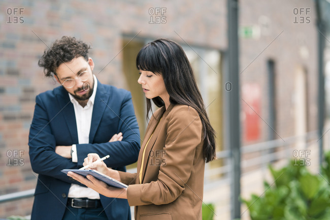Female entrepreneur with digital tablet explaining male colleague at office