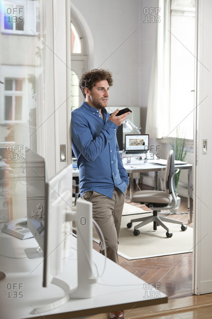 Young businessman sending voicemail through mobile phone at office doorway