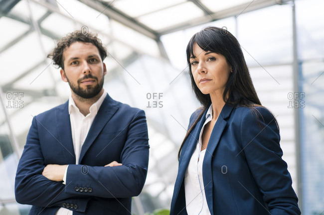 Male entrepreneur with arms crossed standing by confident female colleague