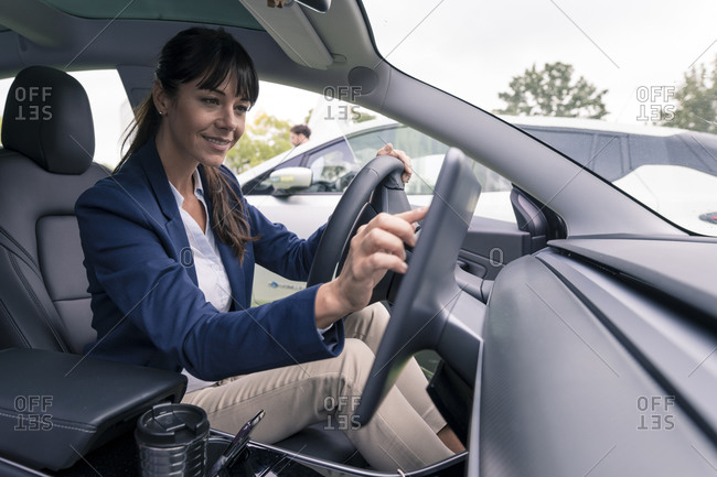 Smiling female entrepreneur navigating through device while sitting in car