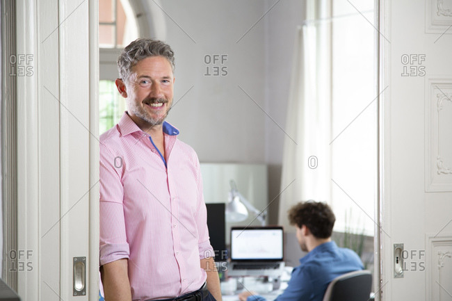 Smiling businessman with  male colleague in background at office cabin