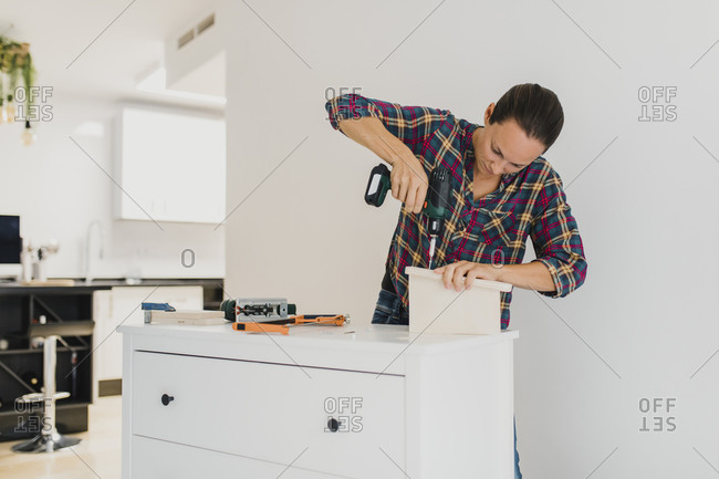 Craftsperson using electric screwdriver while standing by cabinet at home