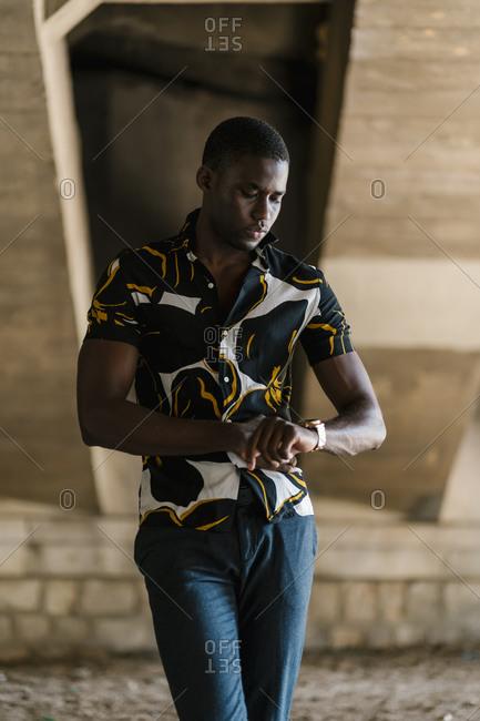 Male entrepreneur checking time on wristwatch while standing below bridge