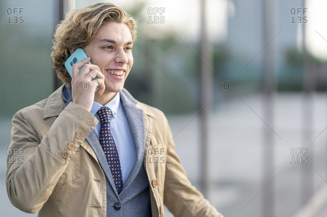 Young businessman smiling while talking on mobile phone standing outdoors