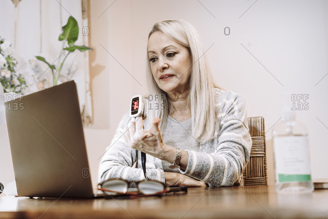 Senior woman showing pulse temperature while online consultation at home
