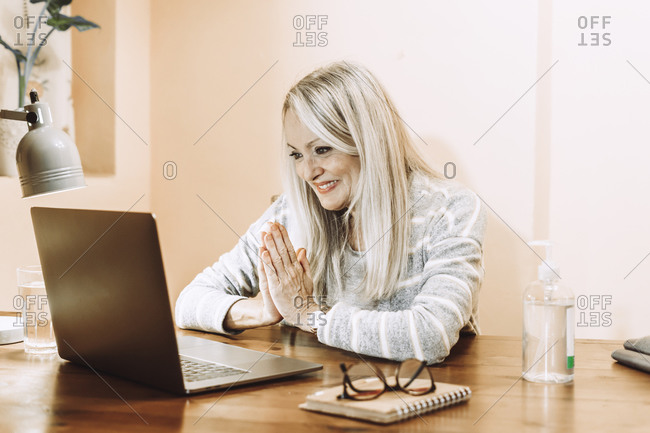 Smiling senior woman greeting during online medical consultation at home