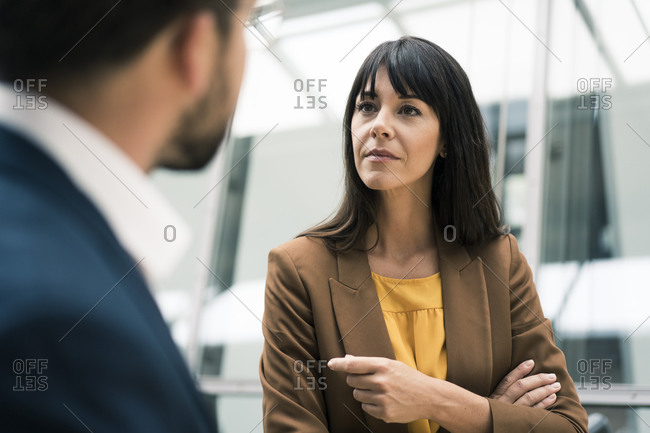 Mature businesswoman discussing with male colleague in meeting at office