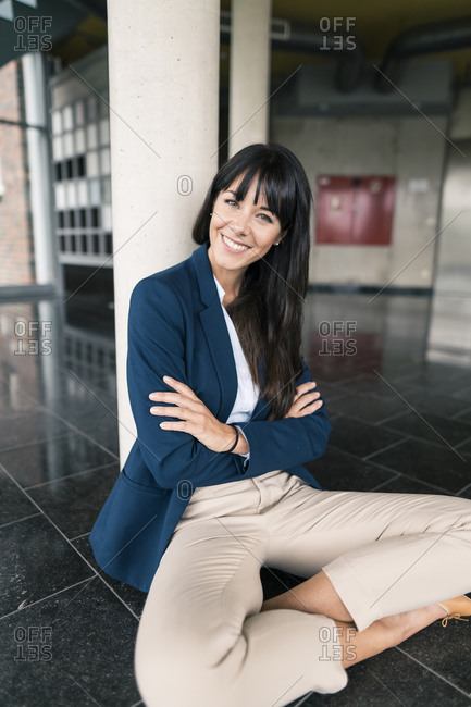 Smiling businesswoman with arms crossed against column in office lobby