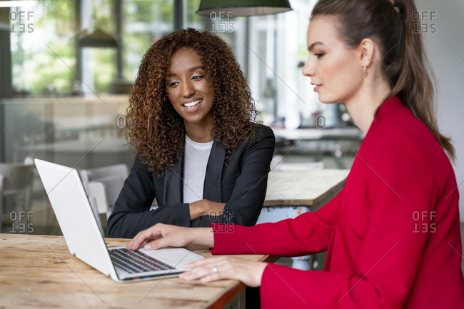 Young female colleagues working together on laptop in office cafeteria