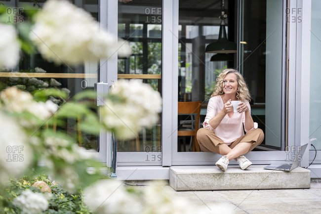 Smiling businesswoman having coffee while sitting at doorway of office