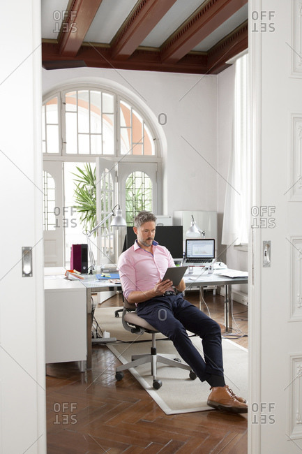 Mature businessman using digital tablet while sitting in office cabin