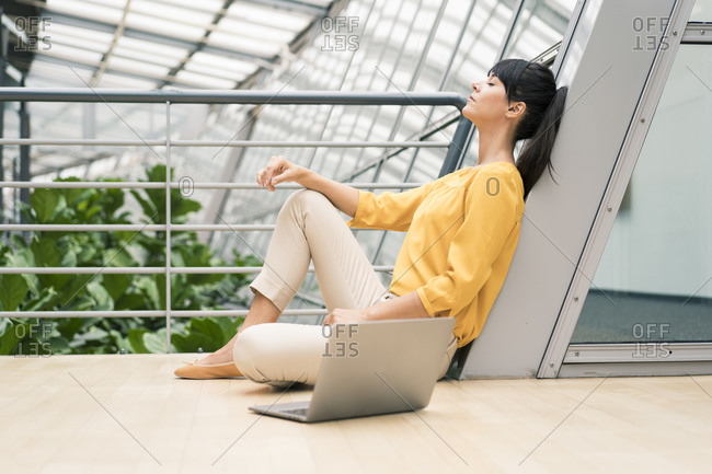 Female entrepreneur sitting by railing with laptop in office corridor