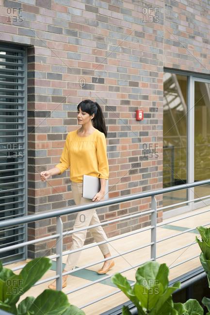 Mature female entrepreneur with laptop walking by railing in corridor