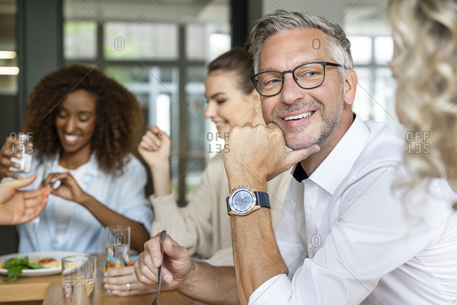 Happy mature businessman looking at female coworker in office kitchen