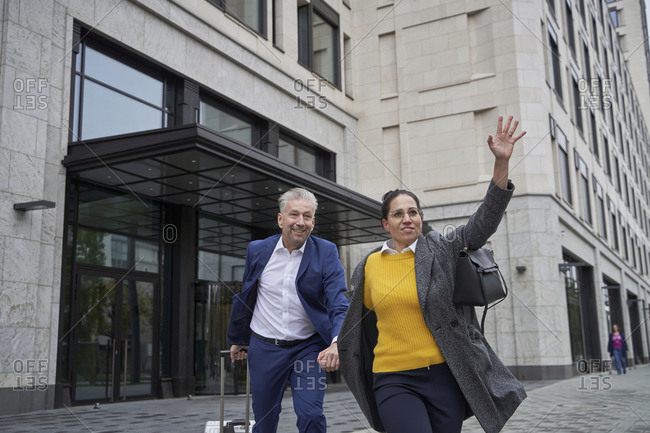 Businesswoman waving hand for taxi walking with colleague on footpath