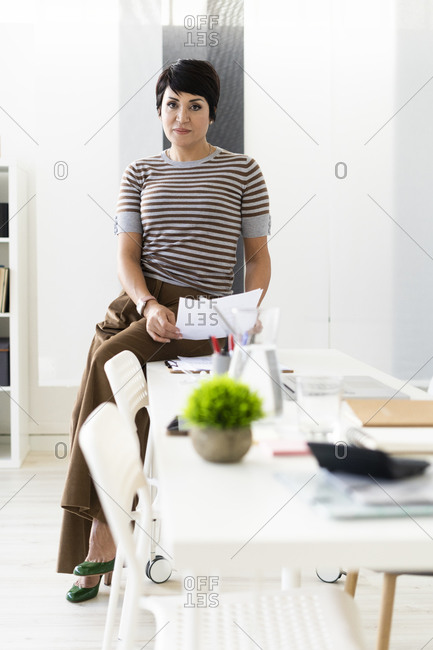 Portrait of businesswoman browsing documents at edge of office table