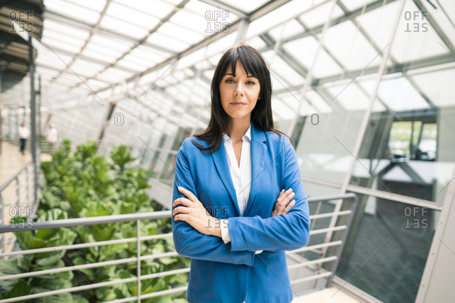 Elegant female entrepreneur with arms crossed in corridor of office