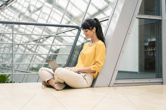 Female entrepreneur sitting by railing while using laptop in office