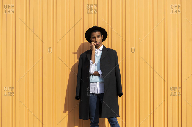Fashionable man with hand on chin standing against corrugated iron