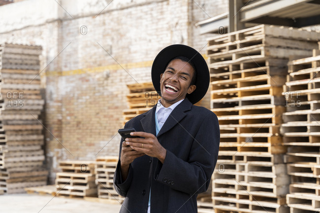 Young man laughing while holding mobile phone against wood pallets