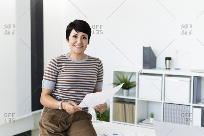 Portrait of businesswoman posing in office with document in hands