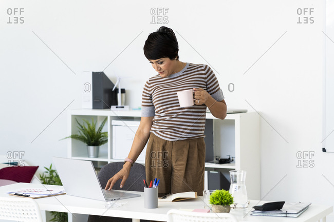 Businesswoman using office laptop while standing with mug in hand