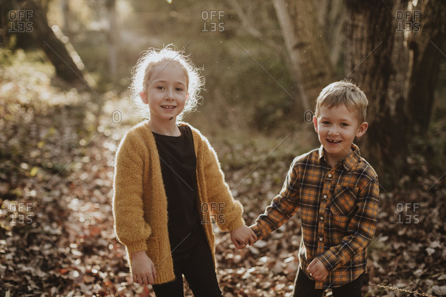Brother and sister smiling while holding hands standing at forest