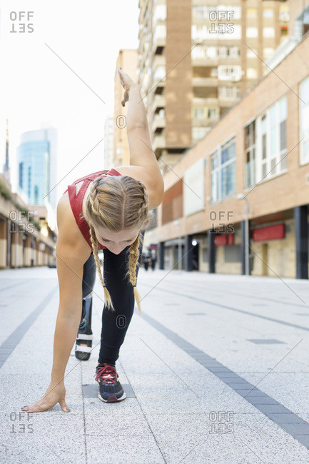 Athlete with prosthetic leg crouching for sports race on footpath