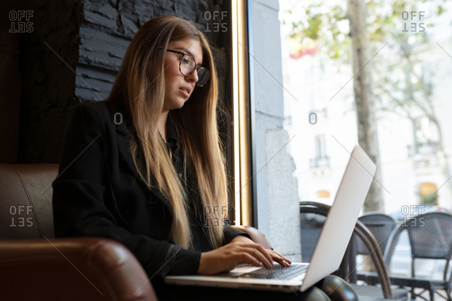 Young woman wearing eyeglasses using laptop while sitting at cafe