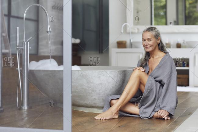 Smiling mature woman sitting by bathtub on floorboard in bathroom