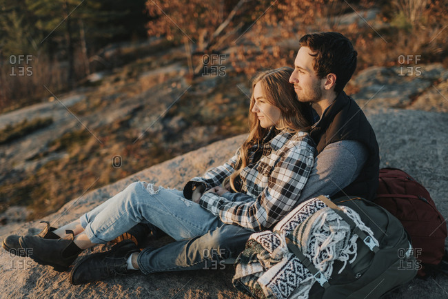Young couple sitting together on rocky surface during autumn hike