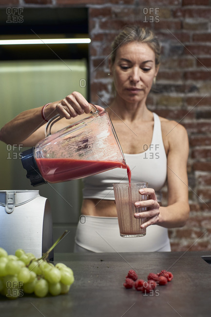Mature woman pouring raspberry fruit smoothie in glass at kitchen