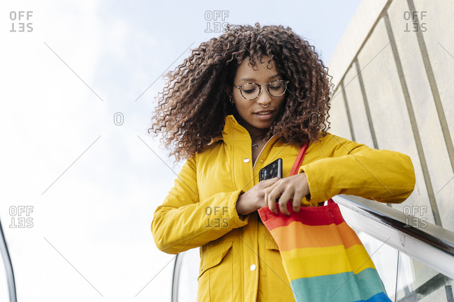 Woman searching in purse while standing on escalator against sky