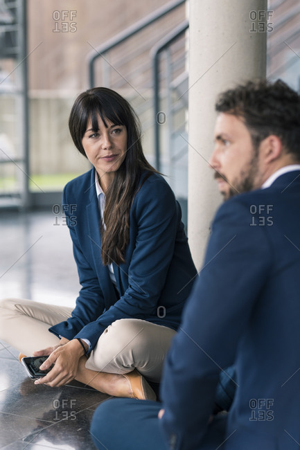 Female entrepreneur sitting by male colleague at lobby in office