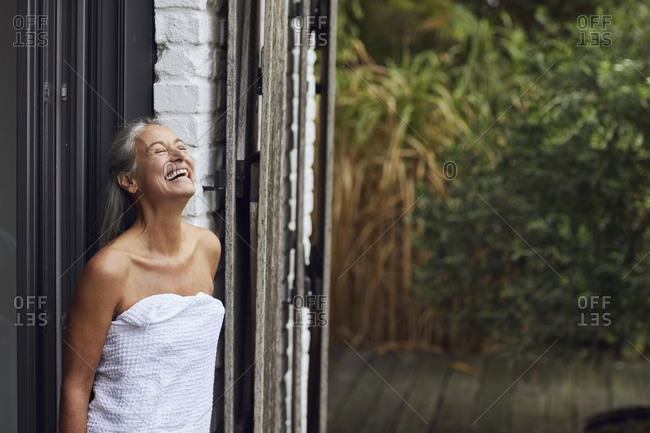 Cheerful mature woman wearing towel standing at doorway of house