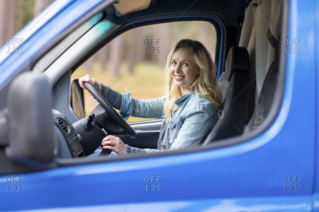 Smiling woman holding steering wheel while sitting in camper van