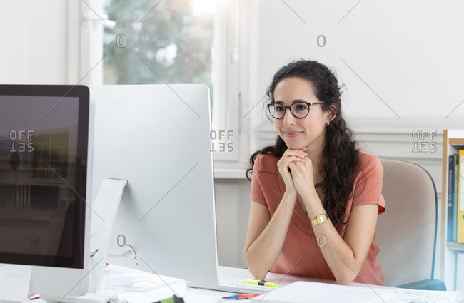 Smiling businesswoman with hand on chin working in office cabin