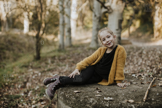 Smiling girl relaxing on concrete bench in forest during autumn