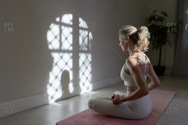 Mature woman practicing lotus position in exercise room at home