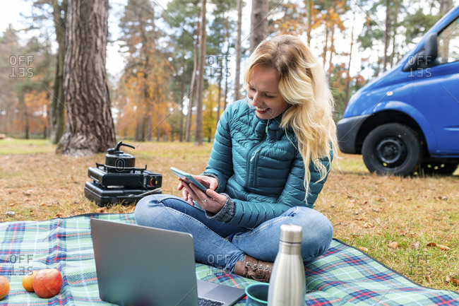 Smiling woman using mobile phone while camping at Cannock Chase